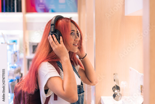 Recess Fitting Music store Asian social influencer woman trying on headphones inside retail store - Happy millennial diverse girl shopping and testing lifestyle music tech products - Technology, electronic and purchase concept.