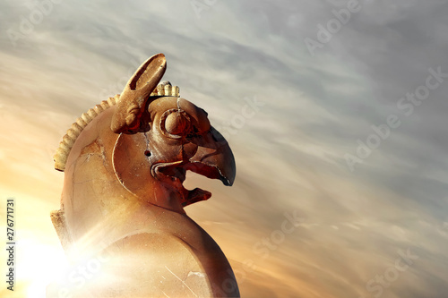 Fotografia  Fragment of stone column sculpture of a Griffin in Persepolis against a blue sky with clouds