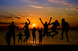 silhouette of friends jumping on beach during sunset time
