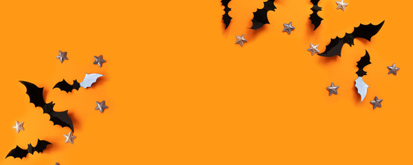 Halloween flat lay composition of black paper bats fly up and gold stars on an orange background