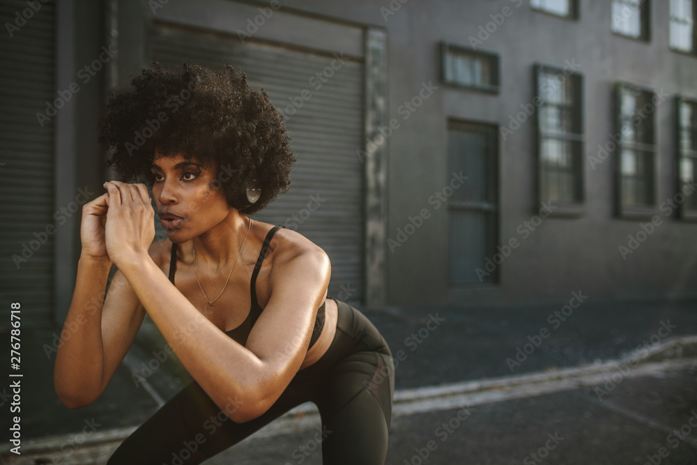 Fototapety, obrazy: Young woman exercising squats in city