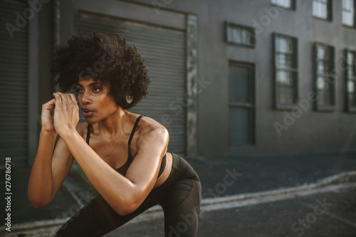 plakat Young woman exercising squats in city