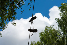 Old Sneakers Hanging On Wires In The Summer On A Background Of Clouds And Branches Of Birch Trees