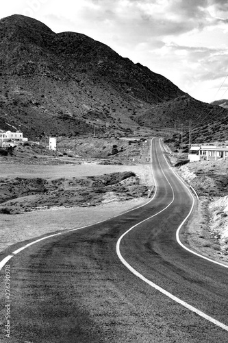 ROAD AND MOUNTAINS IN THE HORIZON. BLACK AND WHITE PHOTOGRAPHY