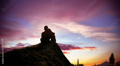 Photo  young couple sitting on the hill watching the sunset