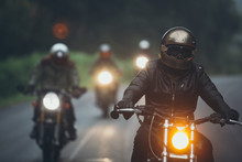 A Group Of Motorcyclists Are T...