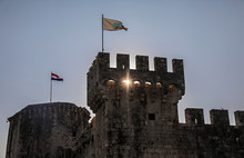 A Turret Of A Castle With Flags Waving At Sunset. Trogir, Croatia.