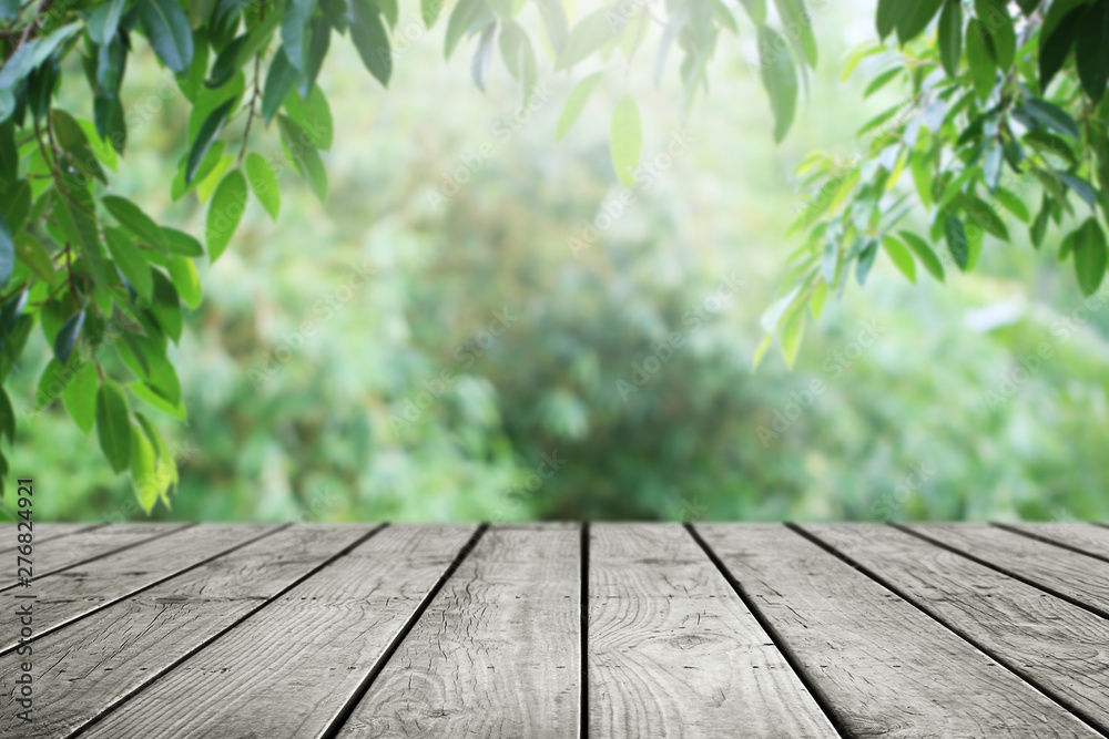 Fototapety, obrazy: Wooden table and blurred green leaf nature in garden background.