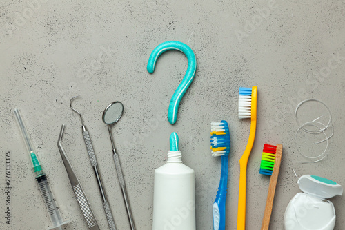 Toothpaste in the form of a question mark and many different and colored toothbrushes and dental floss, dental tool. Concept of how to choose the right toothbrush or how to brush your teeth