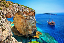 """Tourist Boat Passing Next To Trypitos (also Known As """"Kamara""""), A Natural Rocky Arch At Paxos Island, Ionian Sea, GREECE. In The Background, Antipaxos Island."""