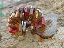 Several Pad Locks Arranged In A Circle On A Stone Wall