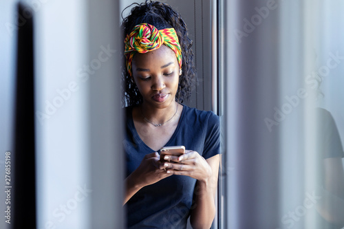 Fotografia  Pretty young woman using her mobile phone while standing next to the window at home