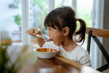 Asian Beautiful Toddler Girl Having Breakfast By Herself In The Morning At Dining Room