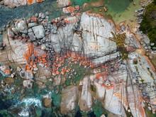 Aerial Of Bay Of Fires Bright Orange Rocks With Waves In Rock Pools In The Sea. Binalong Bay, Tasmania, Australia