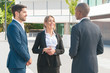 Happy friendly business people discussing project with African American partner. Smiling woman and two men in office suits standing near office building and talking. Business conversation concept