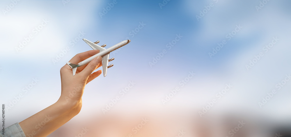 Fototapety, obrazy: Hand holding a plane over blurred city background with sky.Tourism or travel concept