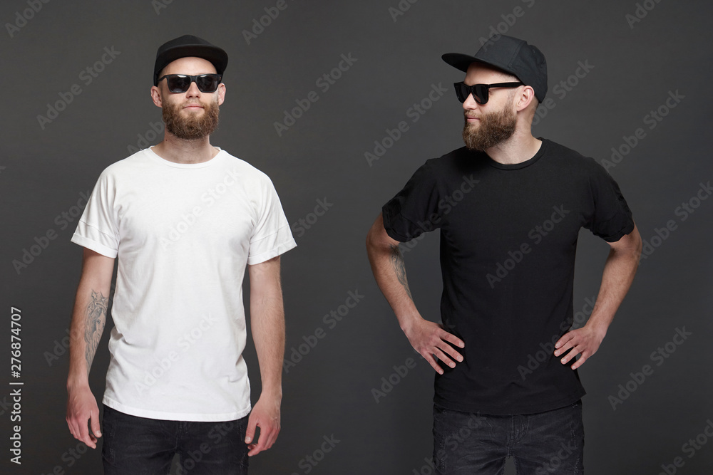 Fototapeta Hipster handsome male model with beard wearing white blank t-shirt and a baseball cap with space for your logo or design in casual urban style.