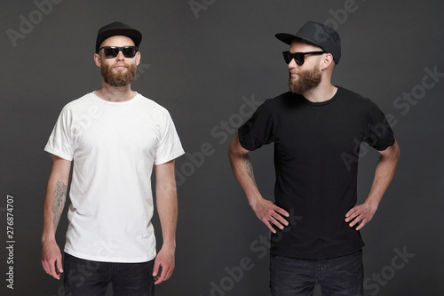 Obraz Hipster handsome male model with beard wearing white blank t-shirt and a baseball cap with space for your logo or design in casual urban style. - fototapety do salonu