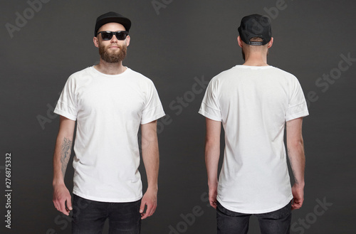 Obraz Hipster handsome male model with beard wearing white blank t-shirt and a baseball cap with space for your logo or design in casual urban style. Front and back view - fototapety do salonu