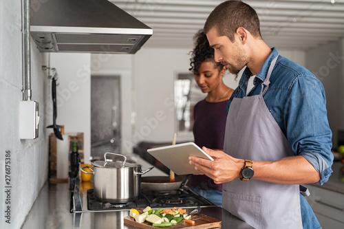Fototapeta Couple cooking togheter with digital tablet obraz