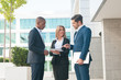 Portrait of multiethnic business team talking about deal outside. Caucasian businessman pointing at documents, businesswoman smiling at him. Partnership concept