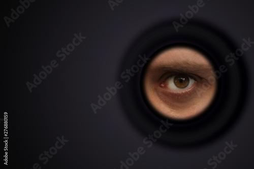 Fotografía  The eye of a man looking out of the eyepiece, the concept of surveillance, peepi