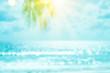Leinwandbild Motiv Blur beautiful nature green palm leaf on tropical beach with bokeh sun light wave abstract background.