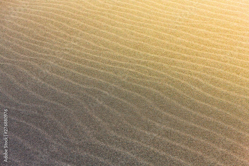 Fotomural  The abstract wave line textures on a Pacific beach illuminated by the Sun and an