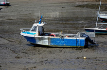 A Blue Small Commercial Vessel Lying On The Sand In A Small Harbor At Low Tide On A Sunny Day. Names And Registrations Have Been Removed.