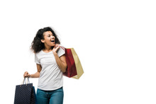 Cheerful Young Curly African American Woman Holding Shopping Bags Isolated On White