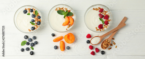 Fotografie, Tablou  Flat lay composition with yogurt desserts and ingredients on white wooden backgr