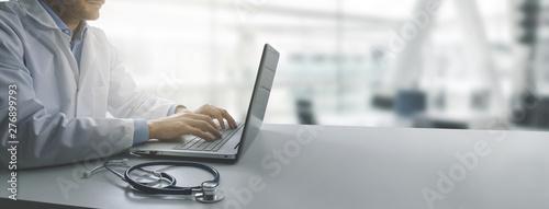 Obraz doctor working on laptop computer in modern clinics office. copy space - fototapety do salonu