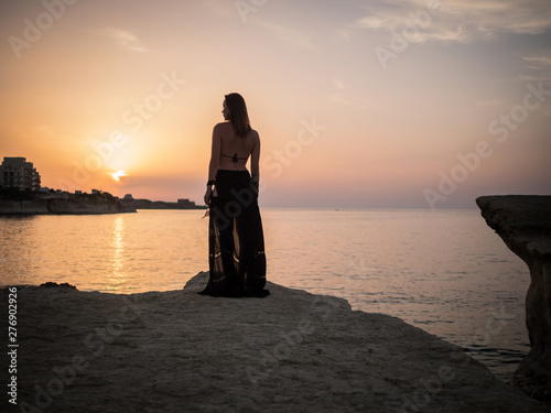 Obraz Woman looking on a resort town at dusk - fototapety do salonu