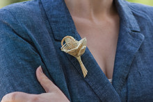 Boutonniere Made Of Straw On A Blue Jacket. Brooch