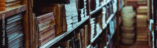 Fotografie, Obraz  panoramic shot of retro books on wooden shelves in library