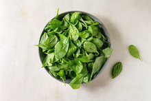 Bowl Of Fresh Baby Spinach Leaves Over White Marble Background. Flat Lay, Copy Space