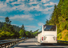 White Tour Bus Or Coach On A Two Lane Motorway Travelling Through A Tree Lined Hilly Countryside On A Sunny Day With Blue Sky.