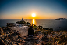 Beautiful Greek Sunset At The Lighthouse On The Island Of Santorini, A Woman Shot From Behind, Watching The Show At Sea From A Rocky Hill