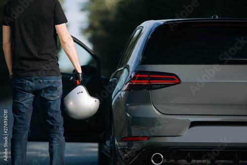 Fototapeta A young man near his modern car prepare for drive