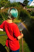 Boy Watering Garden With Hose ...