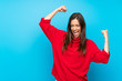 canvas print picture - Young woman with red sweater over isolated blue background celebrating a victory