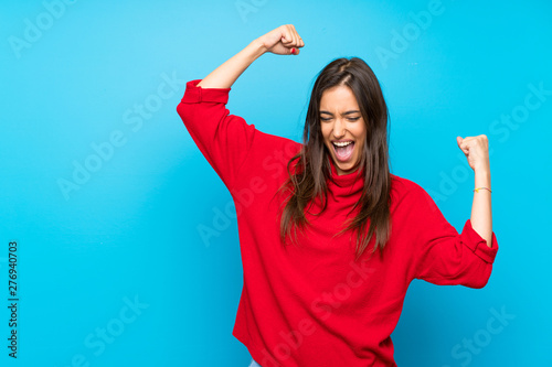 Young woman with red sweater over isolated blue background celebrating a victory Wallpaper Mural
