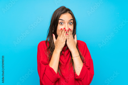 Fotografia, Obraz  Young woman with red sweater over isolated blue background with surprise facial