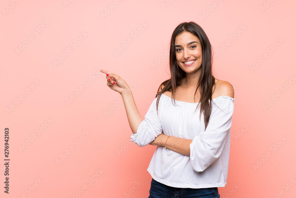 Fototapety, obrazy: Young woman over isolated pink background pointing finger to the side