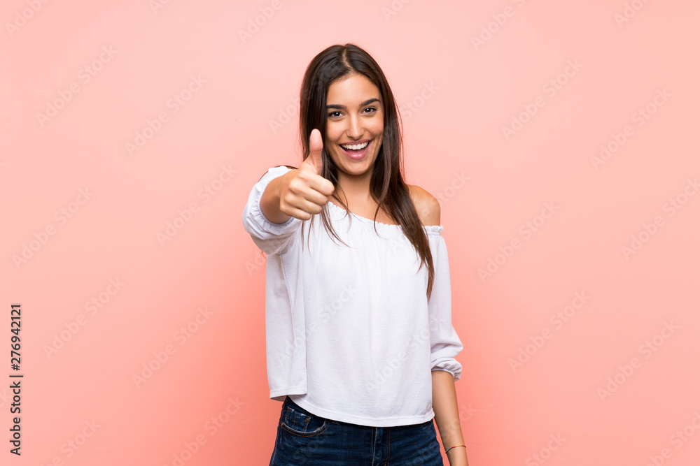 Fototapeta Young woman over isolated pink background with thumbs up because something good has happened