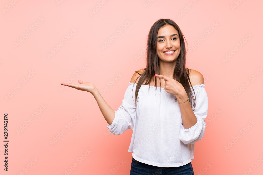 Fototapety, obrazy: Young woman over isolated pink background holding copyspace imaginary on the palm to insert an ad