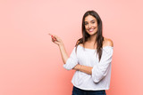 Fototapeta Panels - Young woman over isolated pink background pointing finger to the side
