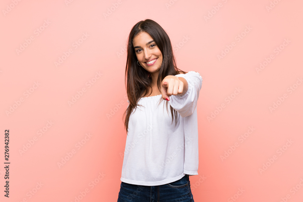 Fototapeta Young woman over isolated pink background points finger at you with a confident expression
