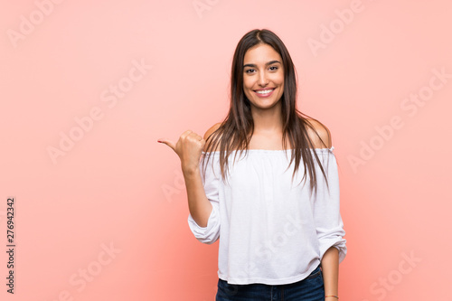 Fotografiet  Young woman over isolated pink background pointing to the side to present a prod