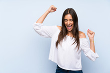 Young Woman Over Isolated Blue Background Celebrating A Victory